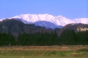 町から見る雪が残る春の飯豊山